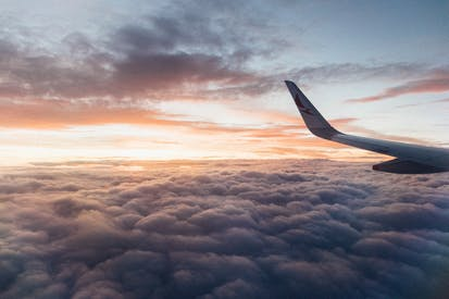 White Airliner Wing On Top Of Sea Clouds