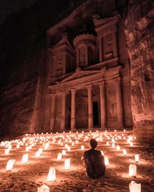 A Man Sitting Outside Of The Famous Petra