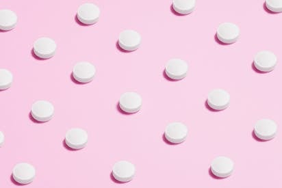White Round Capsule On Pink Background Close Up Photography