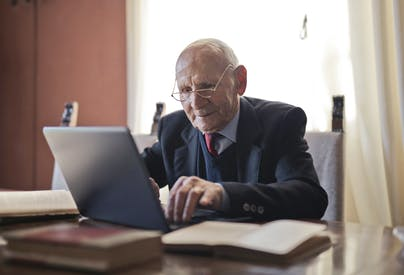 Serious Senior Man Using Laptop While Sitting At Table With Books