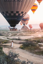 Woman Standing Under Hot Air Balloons