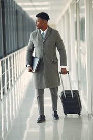 Confident Businessman With Laptop And Suitcase Walking In Airport Hallway