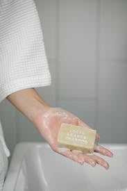 Woman With Wet Soap In Hand In Bathroom