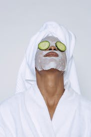 Anonymous Woman With Facial Mask And Cucumber On Eyes