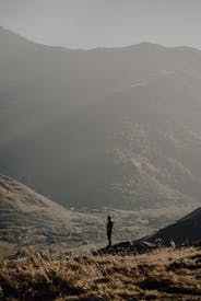 Silhouette Of 2 People Standing On Mountain