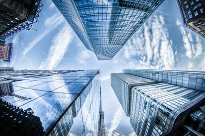 Low Angle Photo Of Four High Rise Curtain Wall Buildings Under White Clouds And Blue Sky