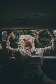 Woman In Gray Long Sleeve Shirt Sitting On Car Seat