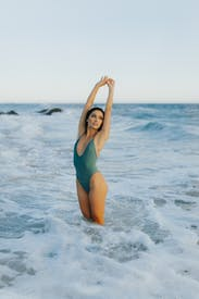 Woman In Blue One Piece Swimsuit Standing On Beach