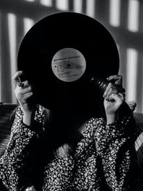 Unrecognized Woman Covering Her Face Behind Black Vinyl Record