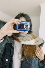 A Female Holding An Analog Camera In Her Face