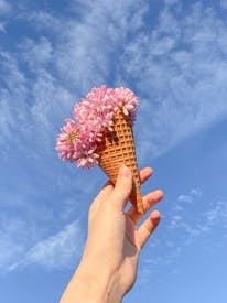 Flowers Being Held In Ice Cream Cone By Woman