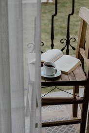Chair With Book And Cup Of Coffee On Balcony
