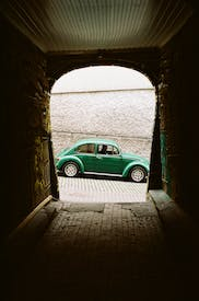 Green Car Parked Beside White Concrete Wall